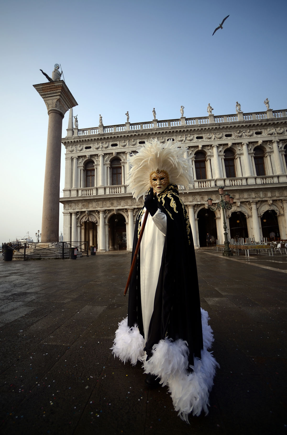 A masked reveller wearing a traditional carnival costume stands in St Mark Square during Venice's Carnival on January 28, 2018.