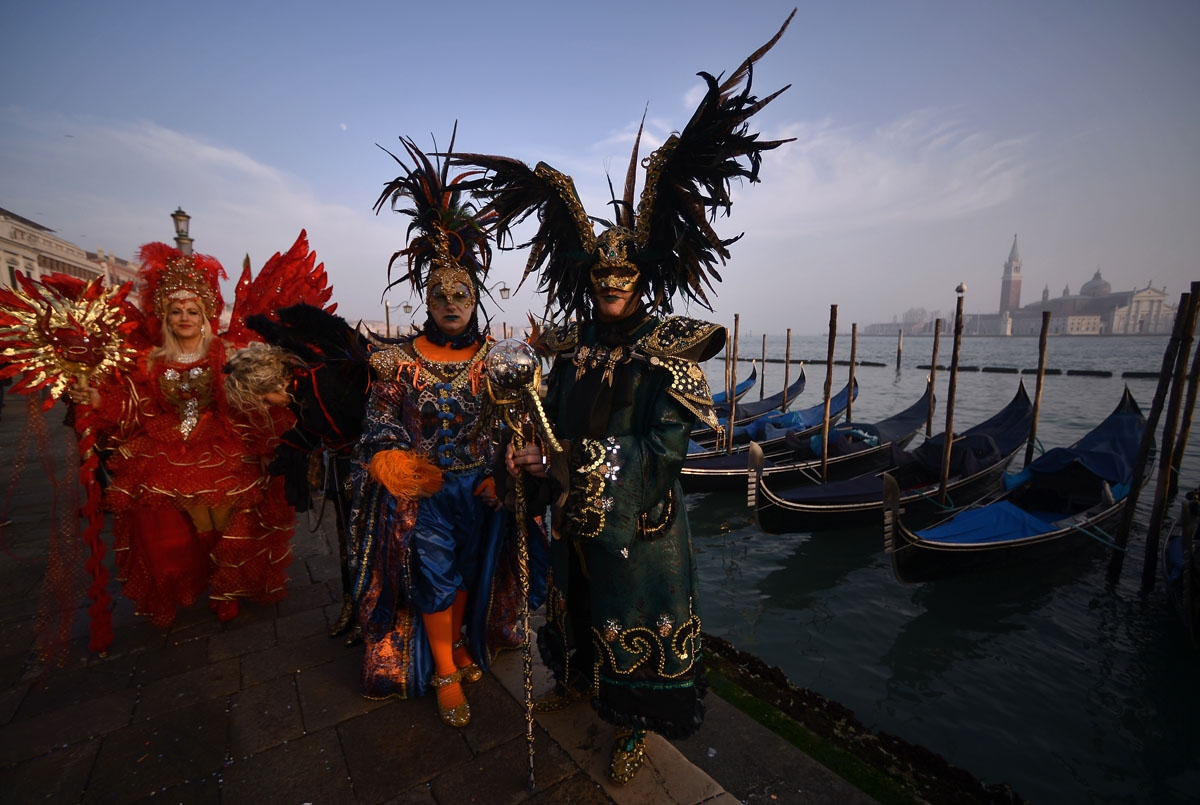 Masked revellers wearing traditional carnival costumes stand in St Mark Square during Venice's Carnival on January 28, 2018.