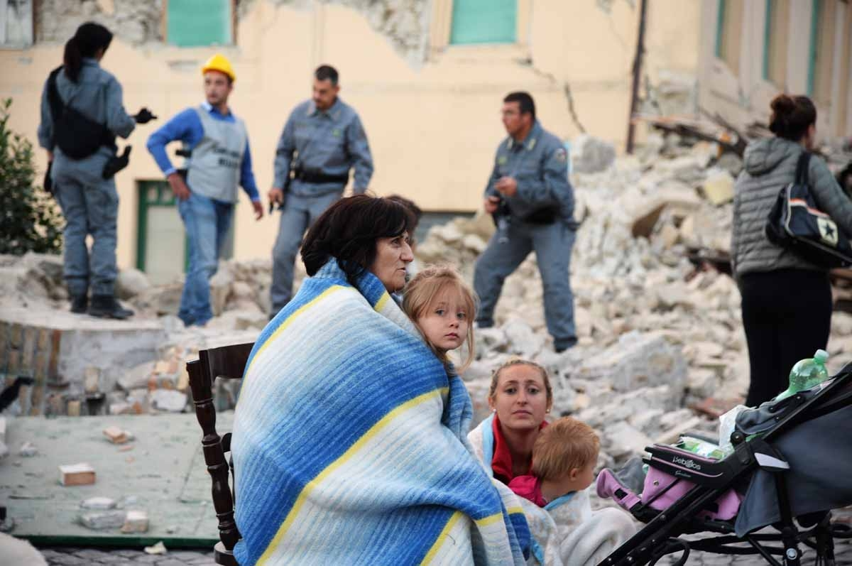 Victims sit among the rubble of a house after a strong earthquake hit Amatrice on August 24, 2016.