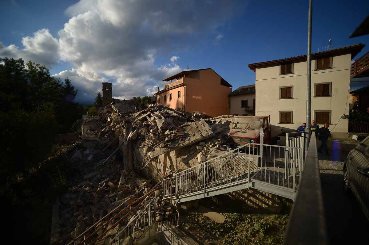 Residents walk past damaged buildings after a strong earthquake hit Amatrice on August 24, 2016.
