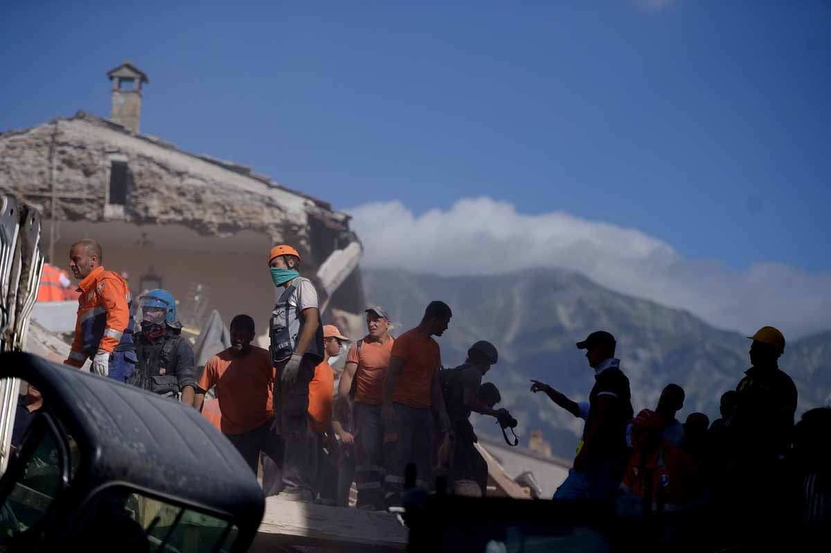 Volunteers work to move rubble and debris during search and rescue operations in Amatrice on August 24, 2016 after a powerful earthquake rocked central Italy.