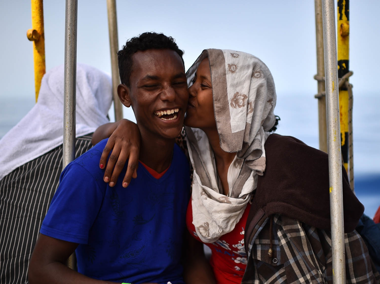 A couple of migrants jokes aboard the rescue ship Aquarius, on May 25, 2016