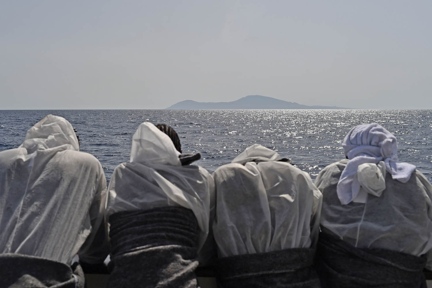 Migrants look at the Pantelleria island from the rescue ship Aquarius, on May 25, 2016