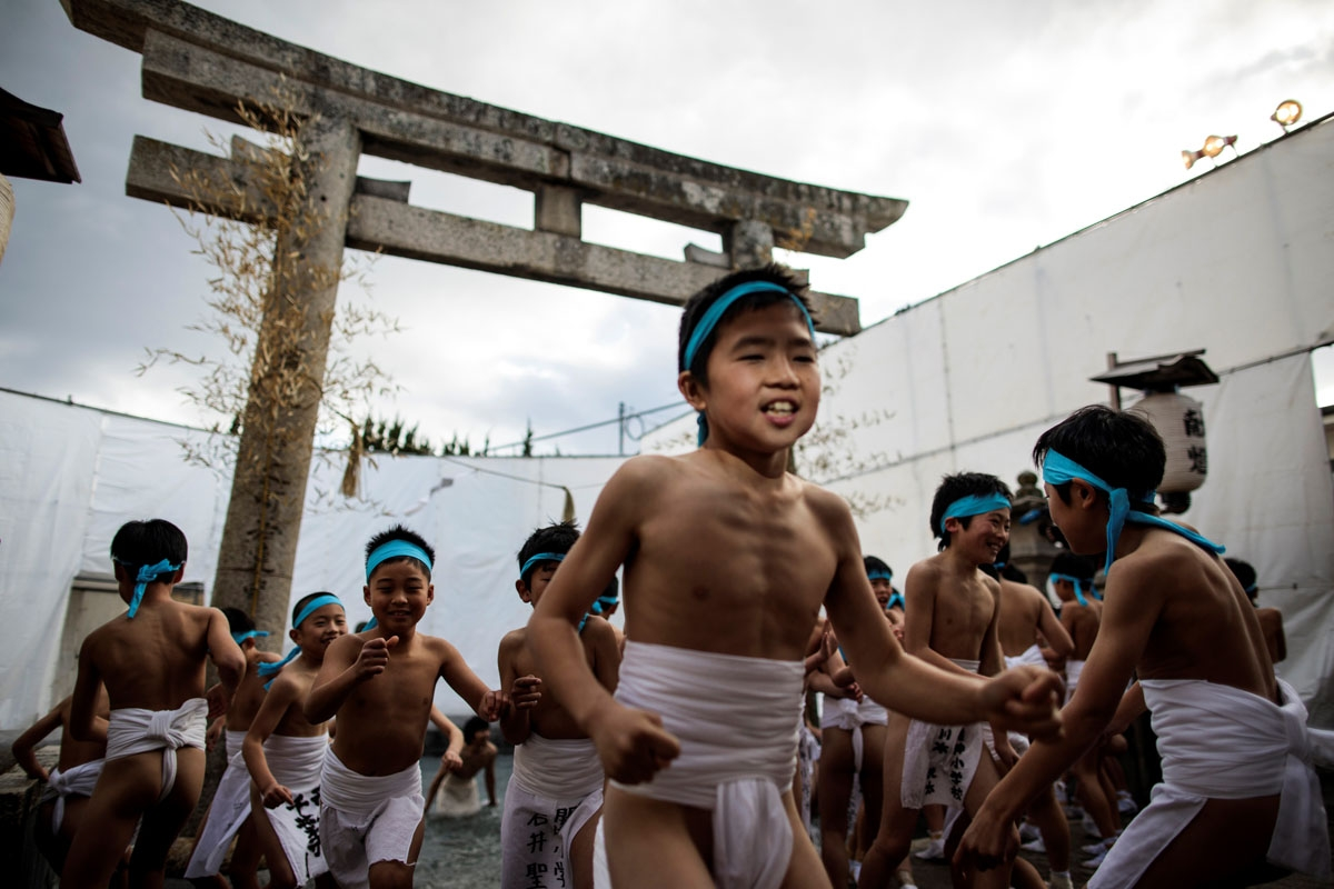 In this picture taken on February 18, 2017, Japanese boys step out of the fountain after being purified during the boys' event in the annual Naked Man Festival or 'Hadaka Matsuri'at Saidaiji Temple in Okayama, western Japan.