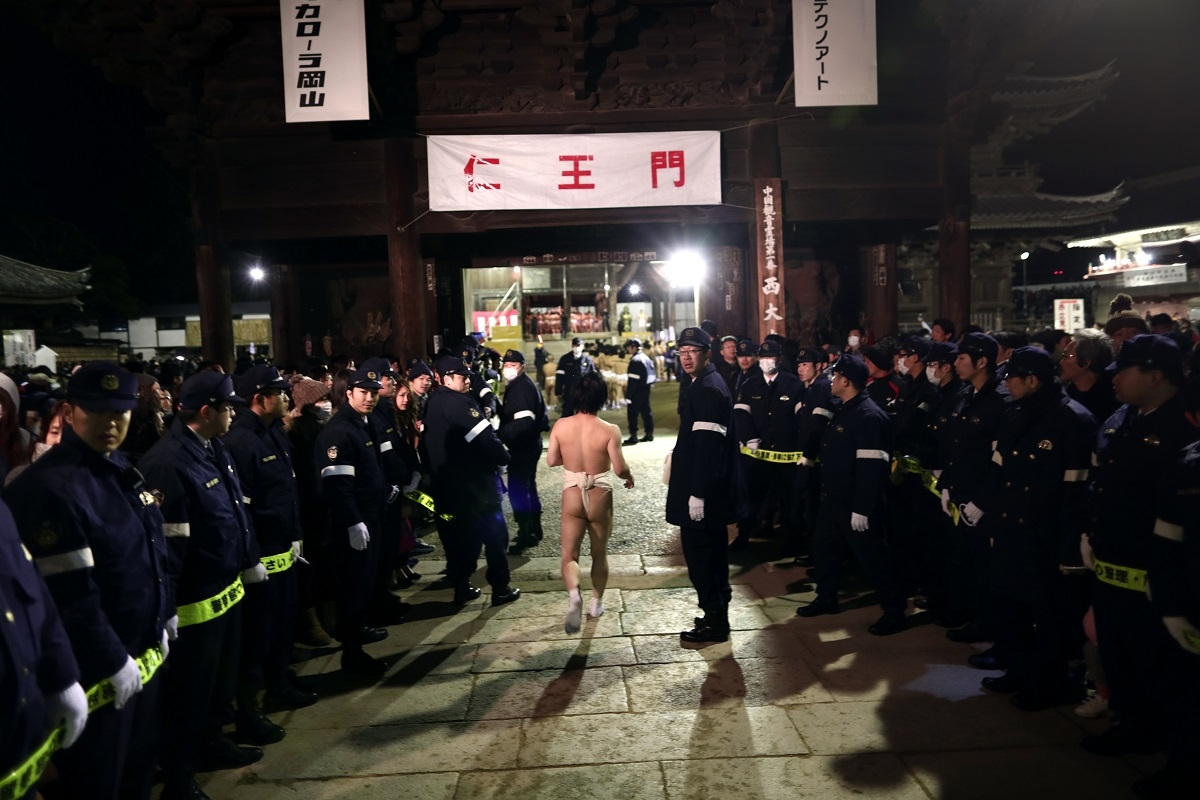 In this picture taken on February 18, 2017, a worshipper runs amid policemen towards Saidaiji Temple to attend the annual Naked Man Festival or 'Hadaka Matsuri' in Okayama, western Japan.With only a skimpy loincloth to protect their modesty, thousands of