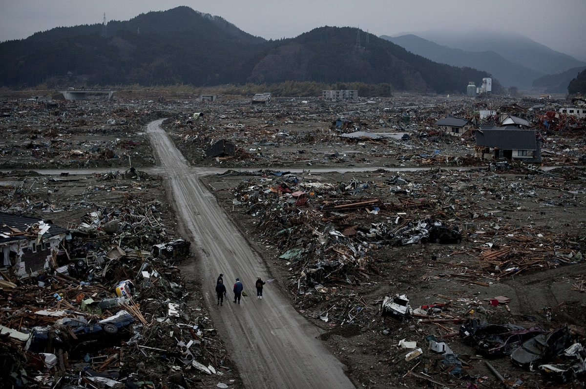 Local residents walk among destroyed houses and debris in the tsunami-damaged city of Rikuzentakata, in Iwate prefecture on March 22, 2011.