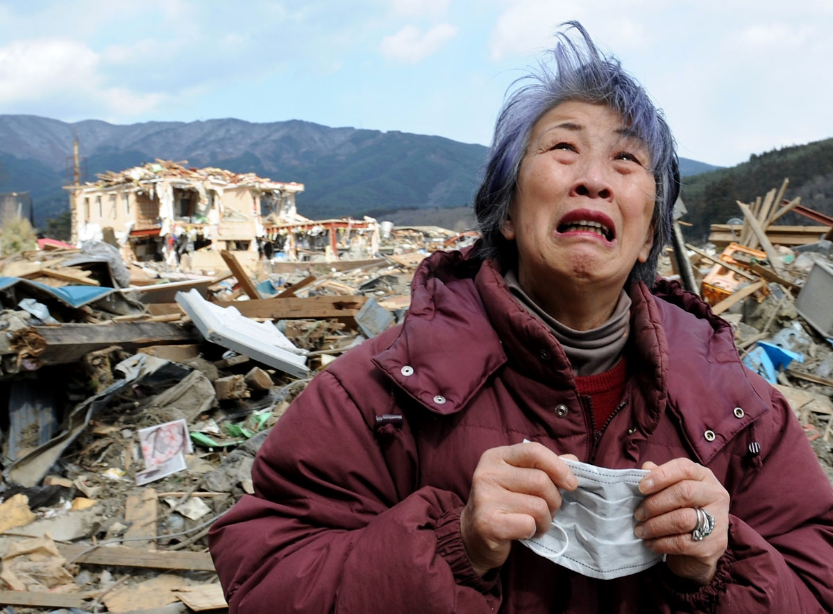An elderly woman cries in front of a destroyed building in the devastated town of Rikuzentakata in Iwate prefecture on March 19, 2011, eight days after a massive 9.0 magnitude earthquake and tsunami hit the northeastern coast of Japan's main island of Hon