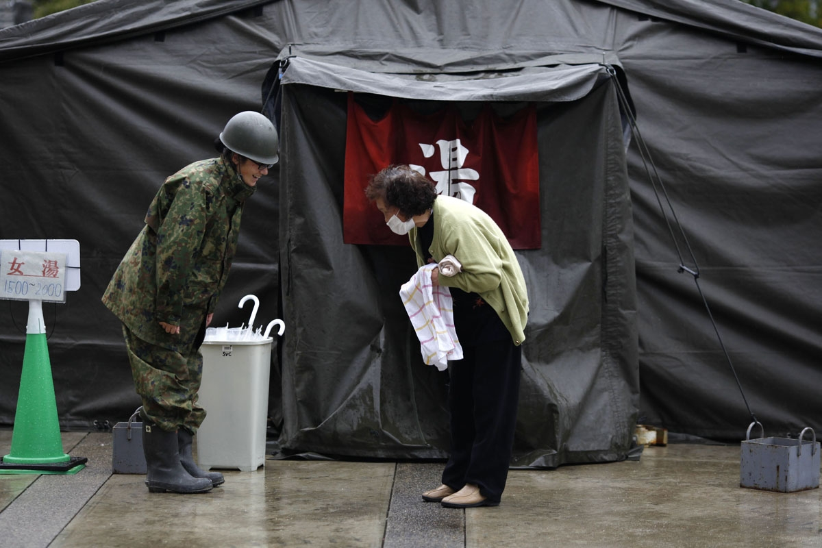 An elderly woman (R) gives thanks to an officer of the Self-Defense Force after she bathed at a temporary hot bath at a shelter in Koryama in Fukushima prefecture on March 21, 2011.