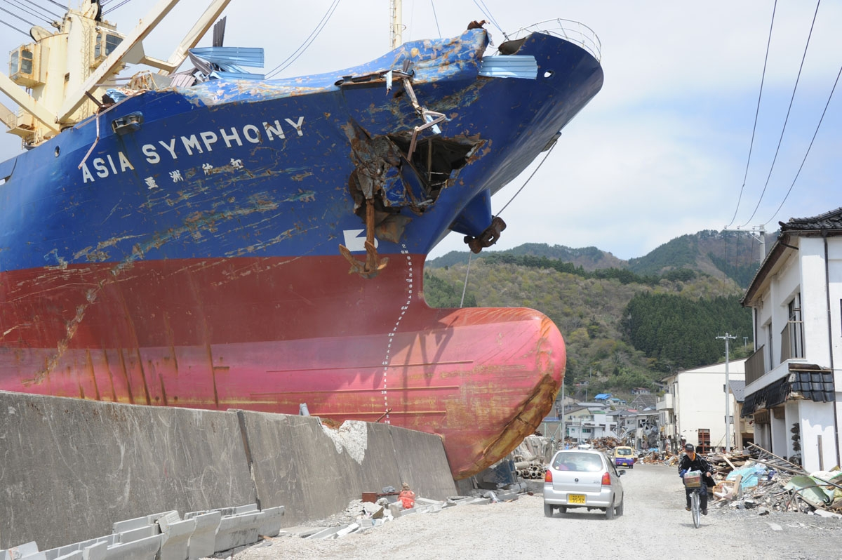 Residents travel on the opened road in front of the 4,724-tonne freighter M.V. Asia Symphony, grounded by the recent tsunami in Kamaishi, Iwate prefecture on May 6, 2011. T