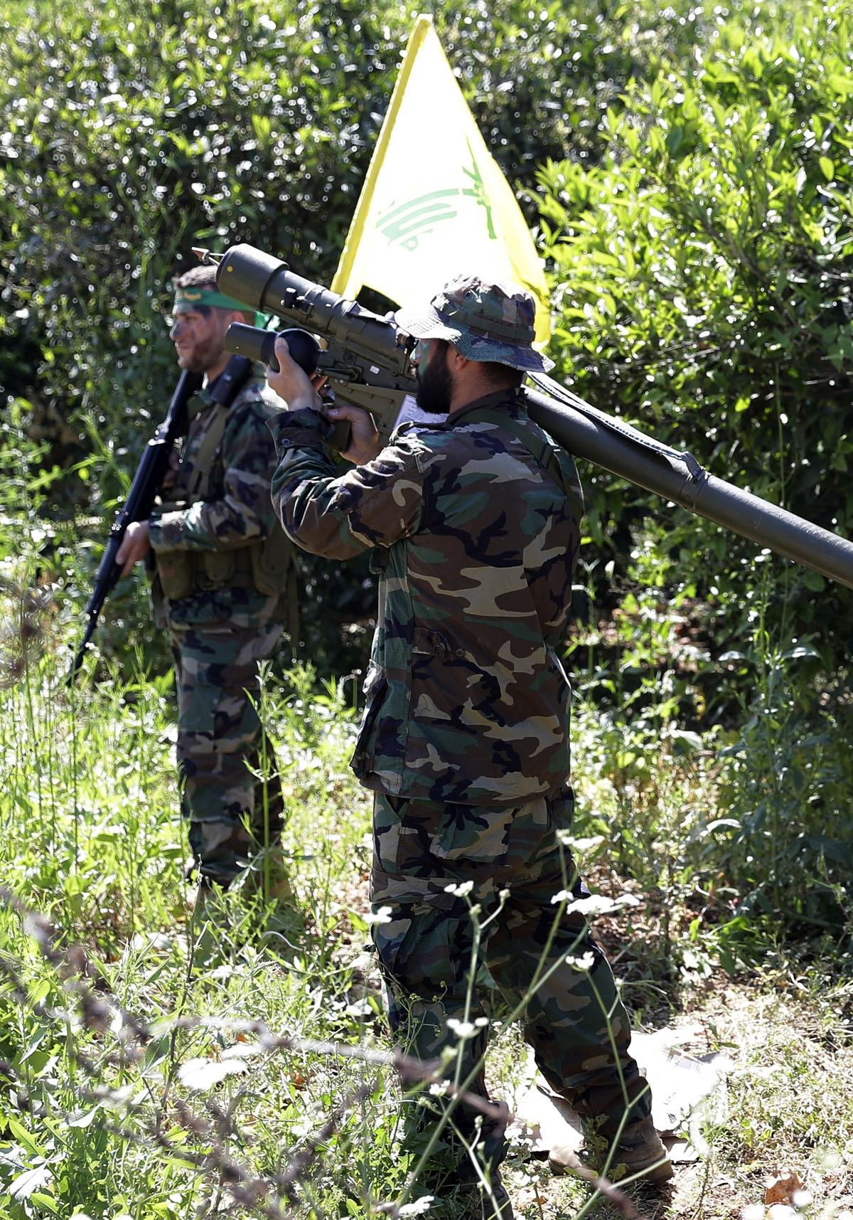 Hezbollah fighters are seen standing at attention in an orange field near the town of Naqura on the Lebanese-Israeli border on April 20, 2017.
