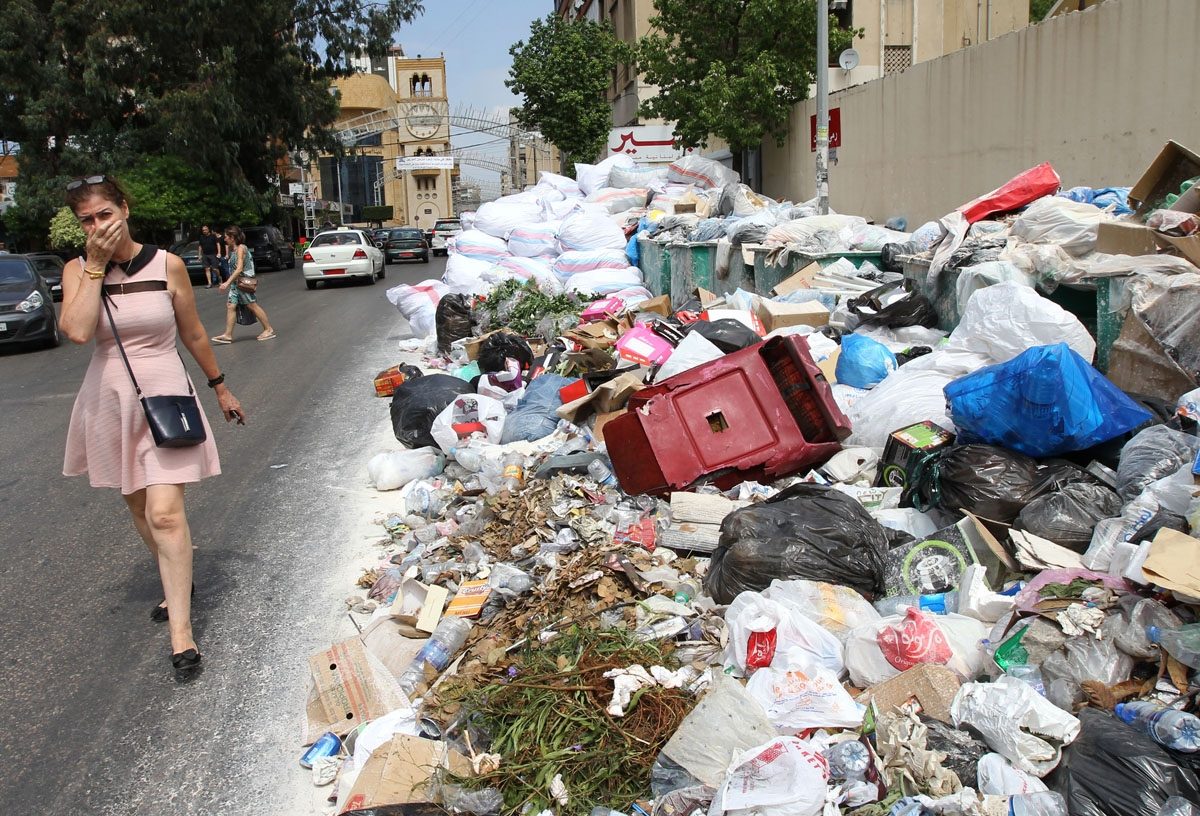 A woman holds her breath as she walks near a temporary garbage dump in the neighbourhood of Jdeideh, northeast of the Lebanese capital Beirut on September 1, 2016