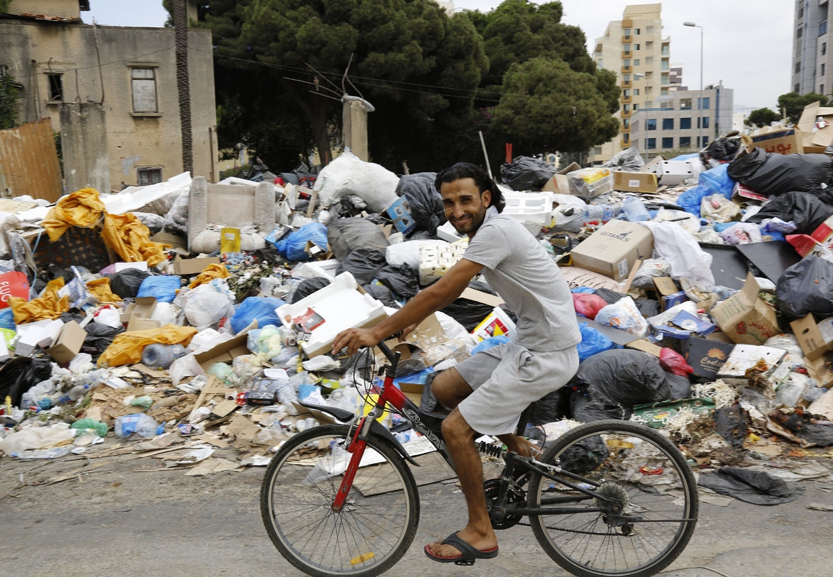 A man rides his bicycle in front of a temporary garbage dump in the neighbourhood Bourj Hammoud, northeast of the Lebanese capital Beirut on September 1, 2016