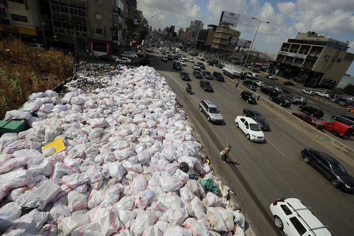 Cars drive by piles of garbage, along the Jdeideh highway, northeast of the Lebanese capital Beirut on September 23, 2016