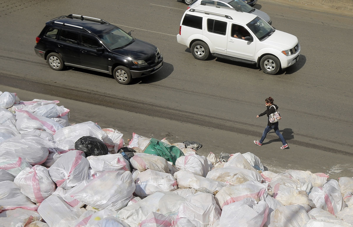 A woman covers her face as she walks past piles of garbage, along the Jdeideh highway, northeast of the Lebanese capital Beirut on September 23, 2016, as the garbage crisis in the country re-emerges.