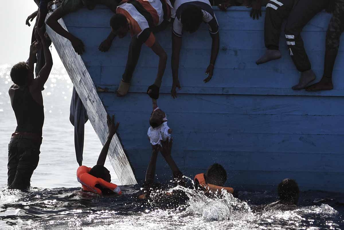 Migrants try to pull a child out of the water as they wait to be rescued by members of Proactiva Open Arms NGO in the Mediterranean sea, some 12 nautical miles north of Libya, on October 4, 2016.