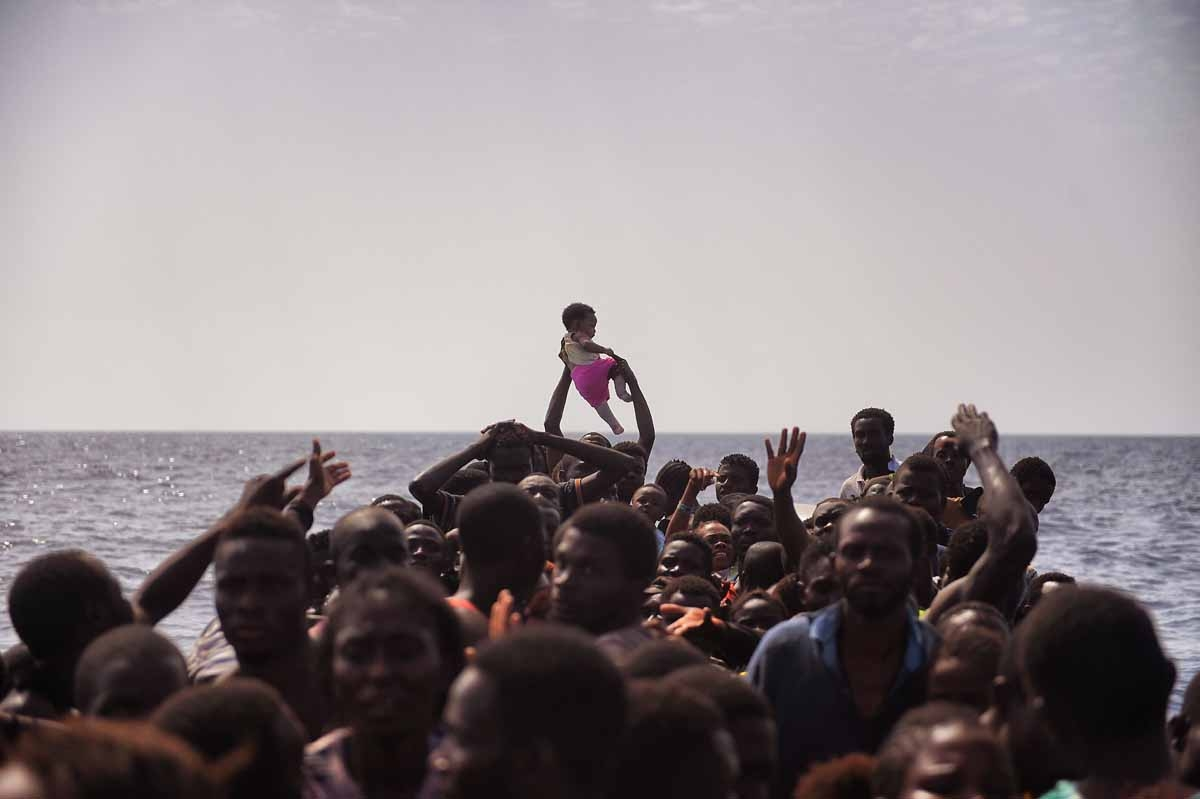 Migrants wait to be rescued by members of Proactiva Open Arms NGO in the Mediterranean Sea, some 12 nautical miles north of Libya, on October 4, 2016.