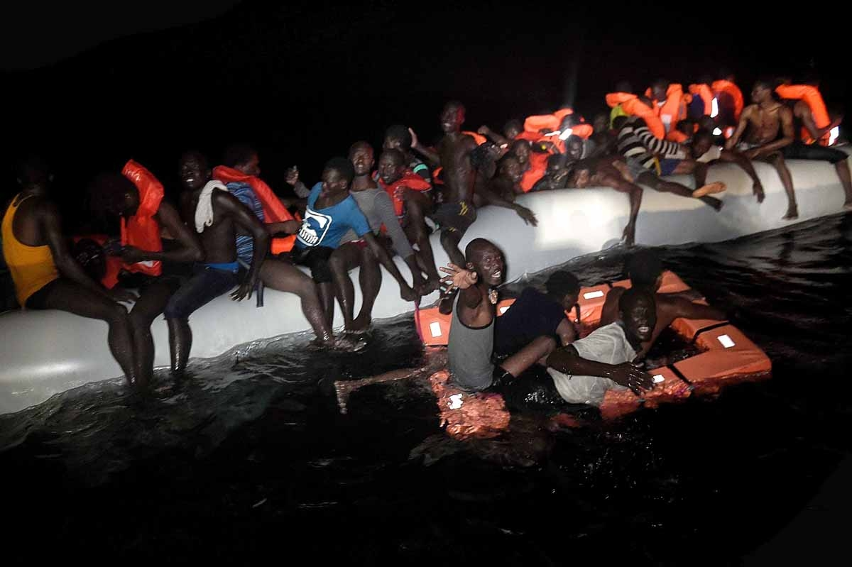 Migrants and refugees wait to be rescued from their sinking rubber boat some eight nautical miles off Libya's Mediterranean coastline on October 12, 2016.