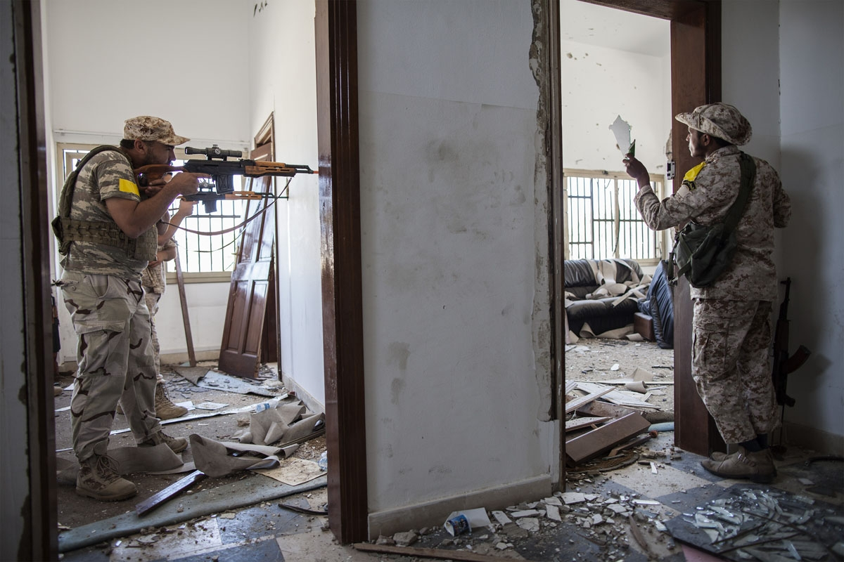 A fighter loyal to Libya's Government of National Accord aims his weapon towards Islamic State (IS) group positions in District 3 while his comrade uses a broken mirror to observe their movement on the western frontline in Sirte on October 2, 2016.