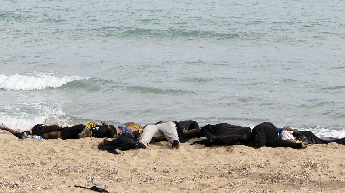 he bodies of illegal migrants are seen lying on the beach in Garabulli, east of the capital Tripoli, on October 6, 2016 after their boat capsized off the shore of Libya.