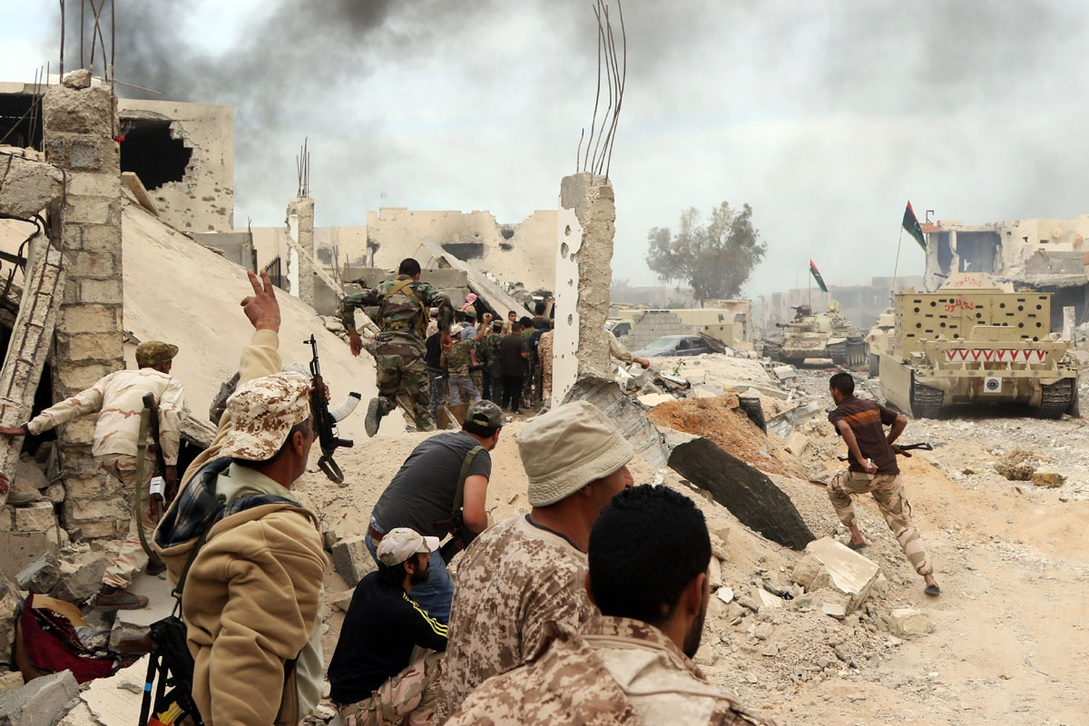 Forces loyal to Libya's Government of National Accord (GNA) hold a position amid the rubble of destroyed buildings in Sirte's Al-Giza Al-Bahriya district on November 21, 2016, during clashes with Islamic State (IS) group jihadists to retake control of the