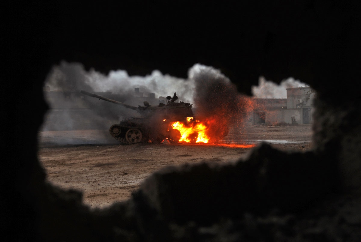 A tank is seen afire during clashes between soldiers from the Libyan National Army, led by Marshal Khalifa Haftar, and jihadist fighters on November 30, 2016 in the area of Qanfudah, south of Benghazi.