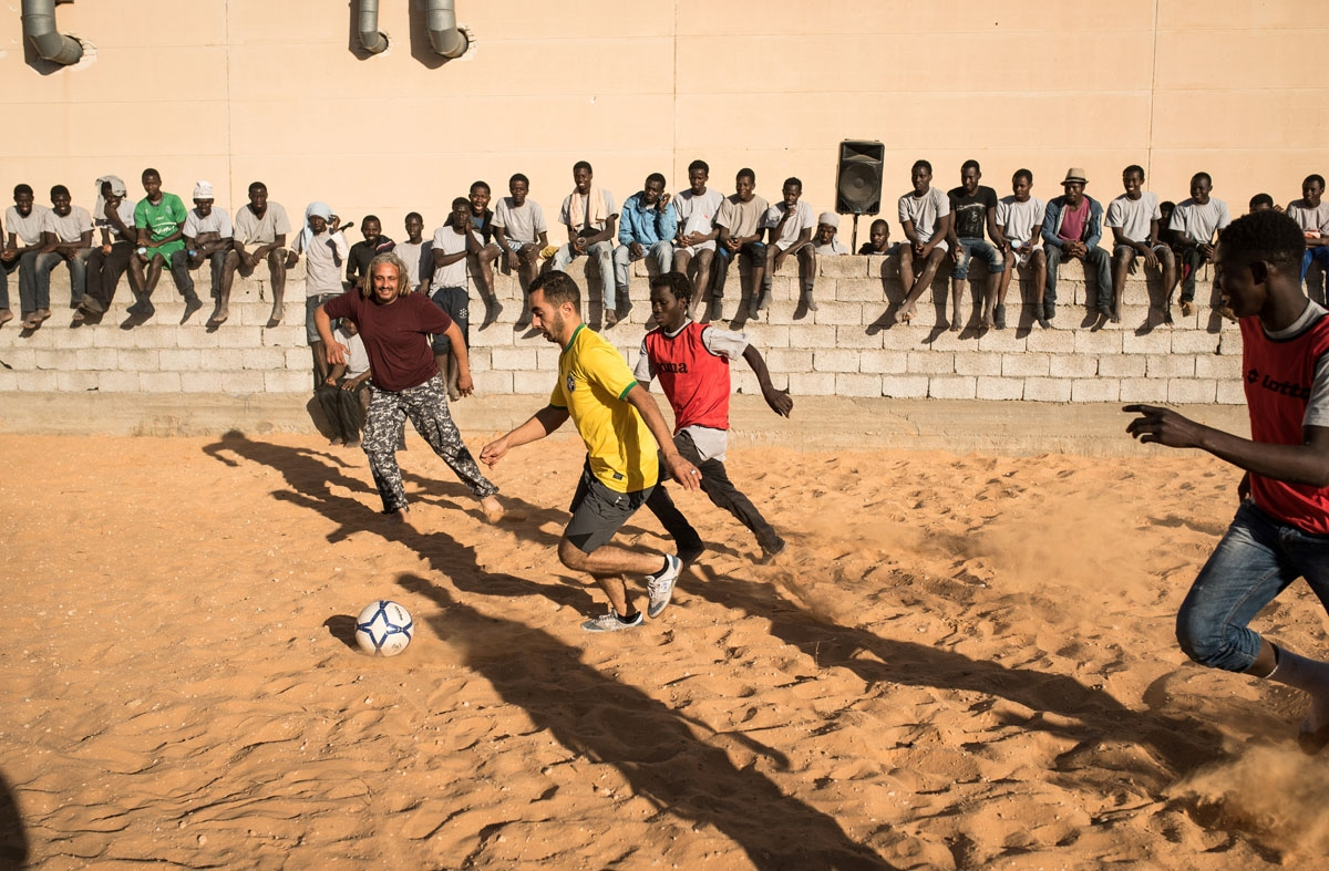 Migrants play football with Libyan guards at the Tariq Al-Matar detention centre on the outskirts of the Libyan capital, Tripoli, on December 18, 2016