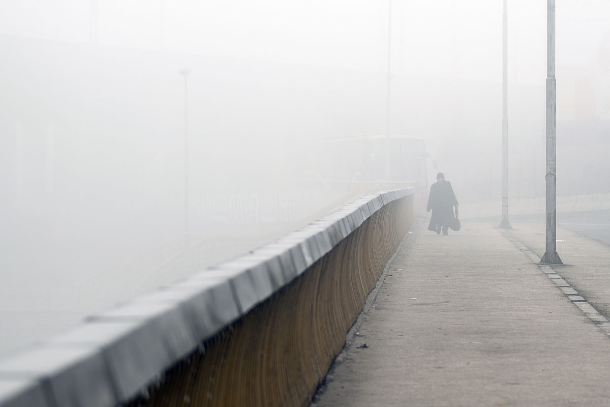 A person walks on a bridge through dense fog in Skopje on December 24, 2015.