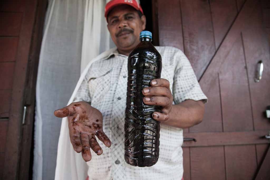 Vanilla farmer Thierry Tommy (L) presents a bottle of pure vanilla essential oil on May 25, 2016 in the municipality of Bemalamatra, 30 kms from Sambava, Madagascar.