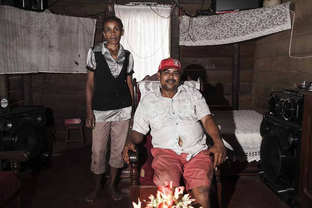Thierry Tommy (R), a vanilla farmer owning about 5 hectares of vanilla plantations and produceing about 3 tons of green vanilla each year with 20 persons working for him, poses with his wife in their living room on May 25, 2016 in the Municipality Bemalam