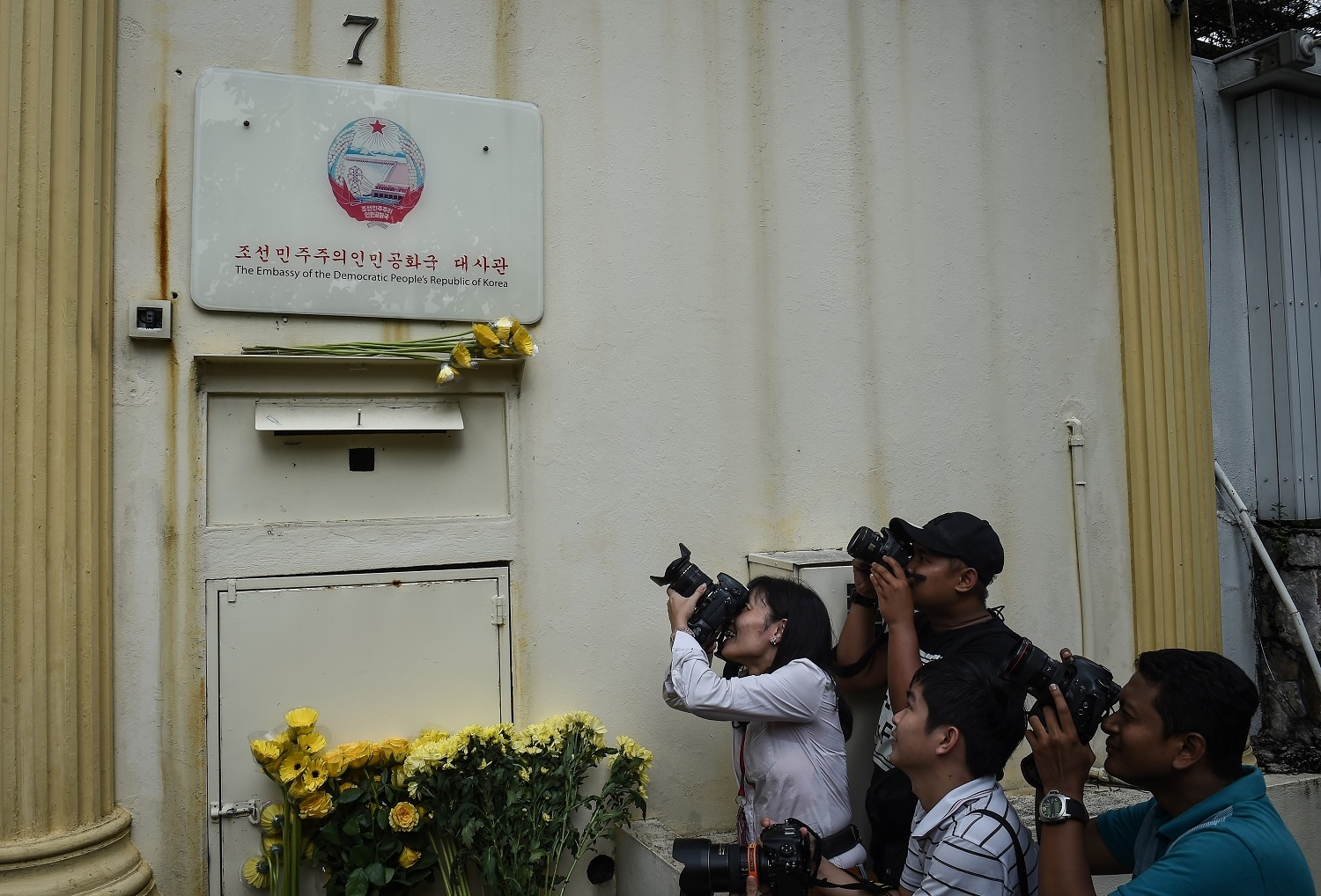 Members of the media take photos of flowers left by Malaysian youth NGO, Solidariti Anak Muda Malaysia, who called for peace and diplomatic cooperation between Malaysia and North Korea, at the North Korean embassy in Kuala Lumpur on March 10, 2017.