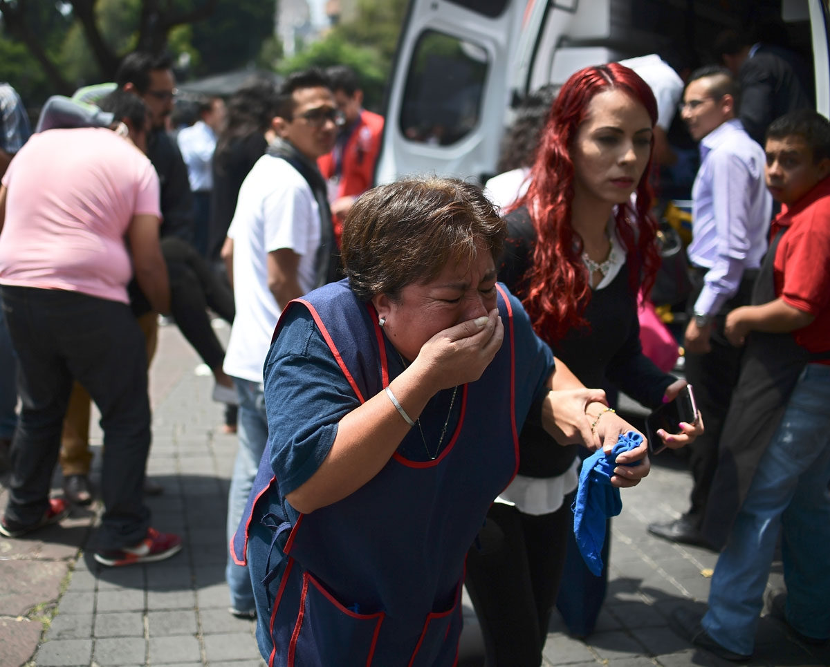 People react after a real quake rattled Mexico City on September 19, 2017 moments after an earthquake drill was held in the capital.