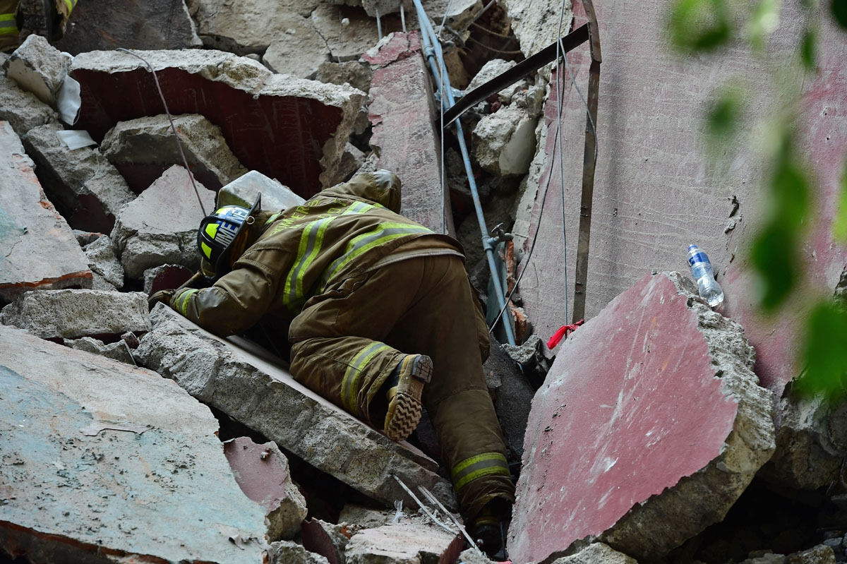 Rescuers, firefighters, policemen, soldiers and volunteers remove rubble and debris from a flattened building in search of survivors after a powerful quake in Mexico City on September 19, 2017. A devastating quake in Mex