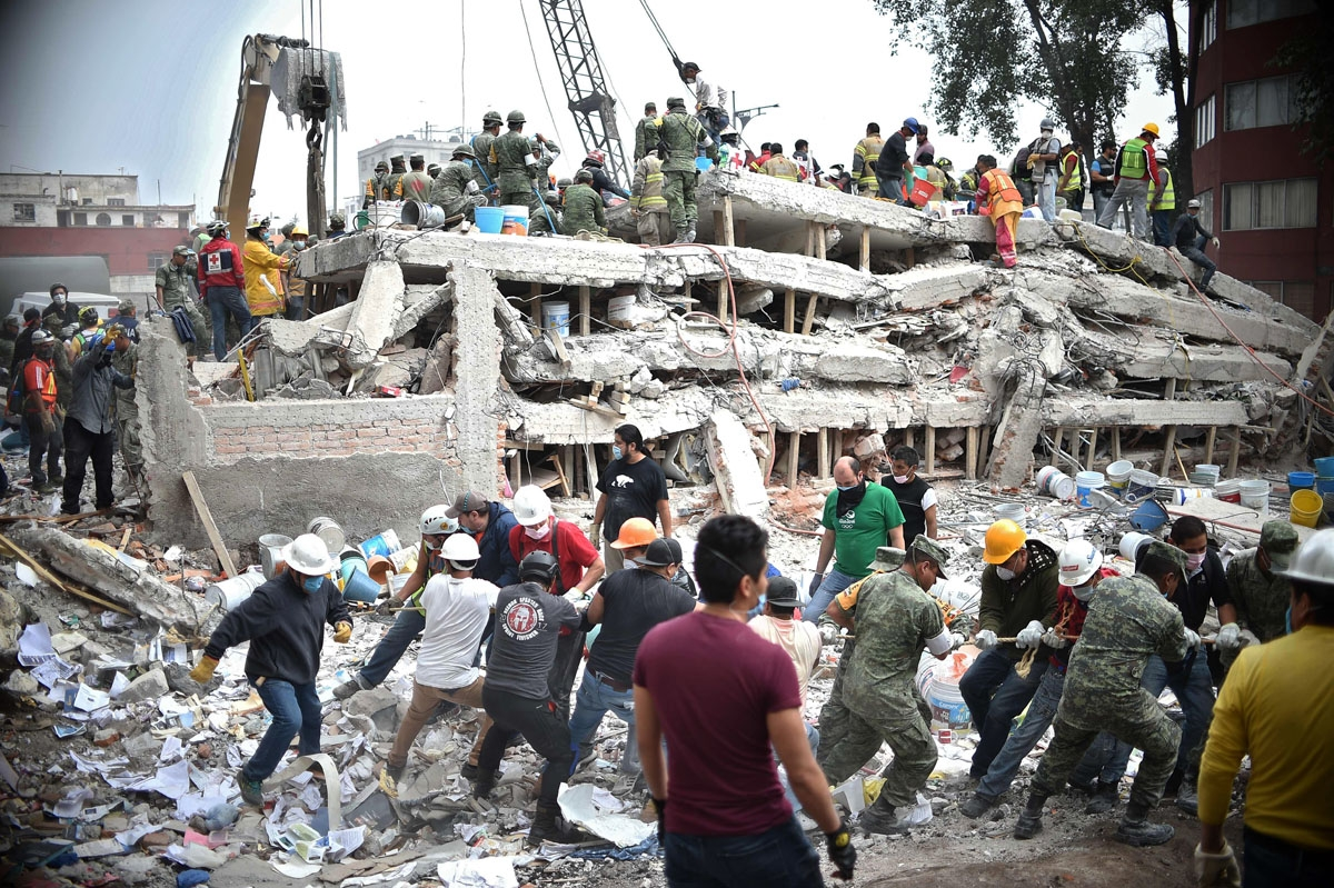 Rescuers, firefighters, policemen, soldiers and volunteers search for survivors in a flattened building in Mexico City on September 20, 2017 a day after a strong quake hit central Mexico. A powerful 7.1 earthquake shook Mexico City on Tuesday, causing pan