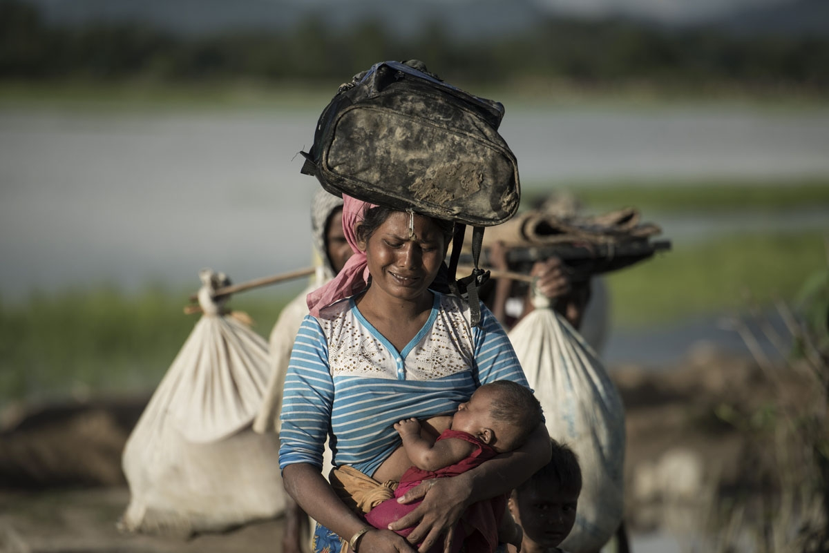 Rohingya refugee cries as she walks after crossing the Naf river from Myanmar into Bangladesh in Whaikhyang on October 9, 2017.