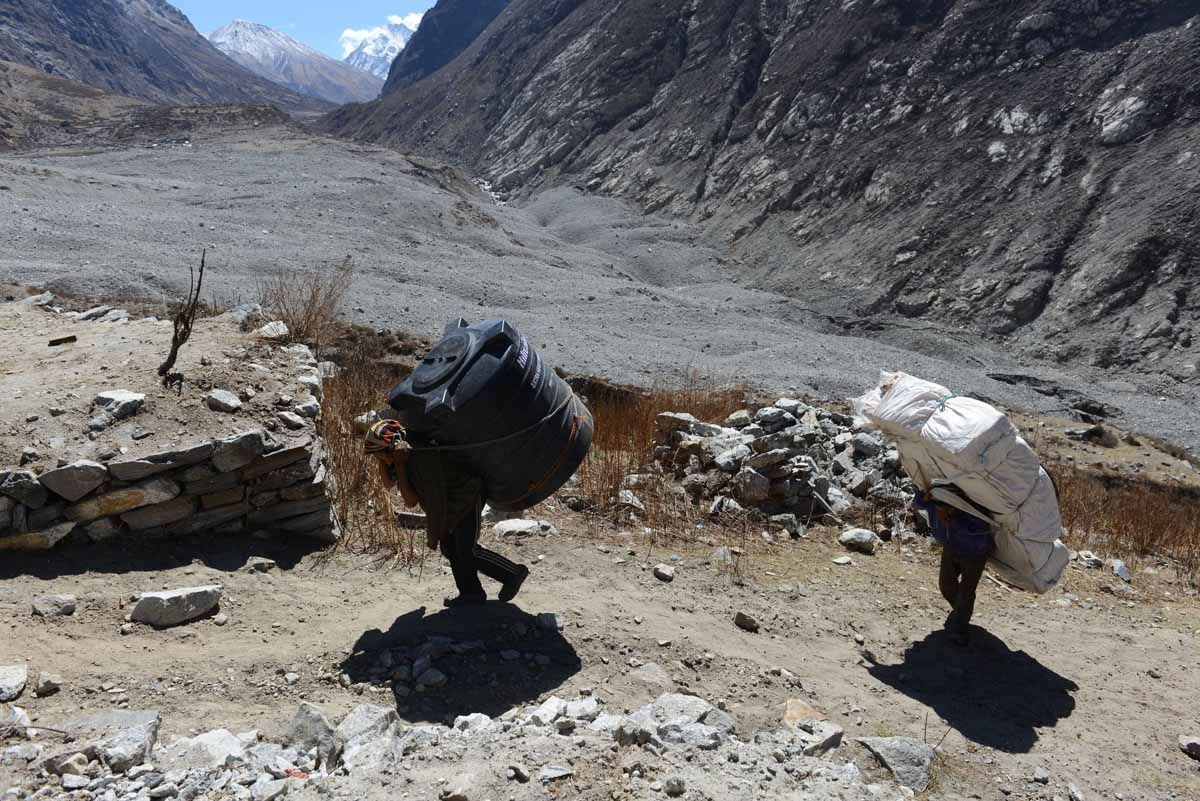 In this photograph taken on April 6, 2016, Nepalese porters carry items to rebuild dwellings in the village of Langtang.