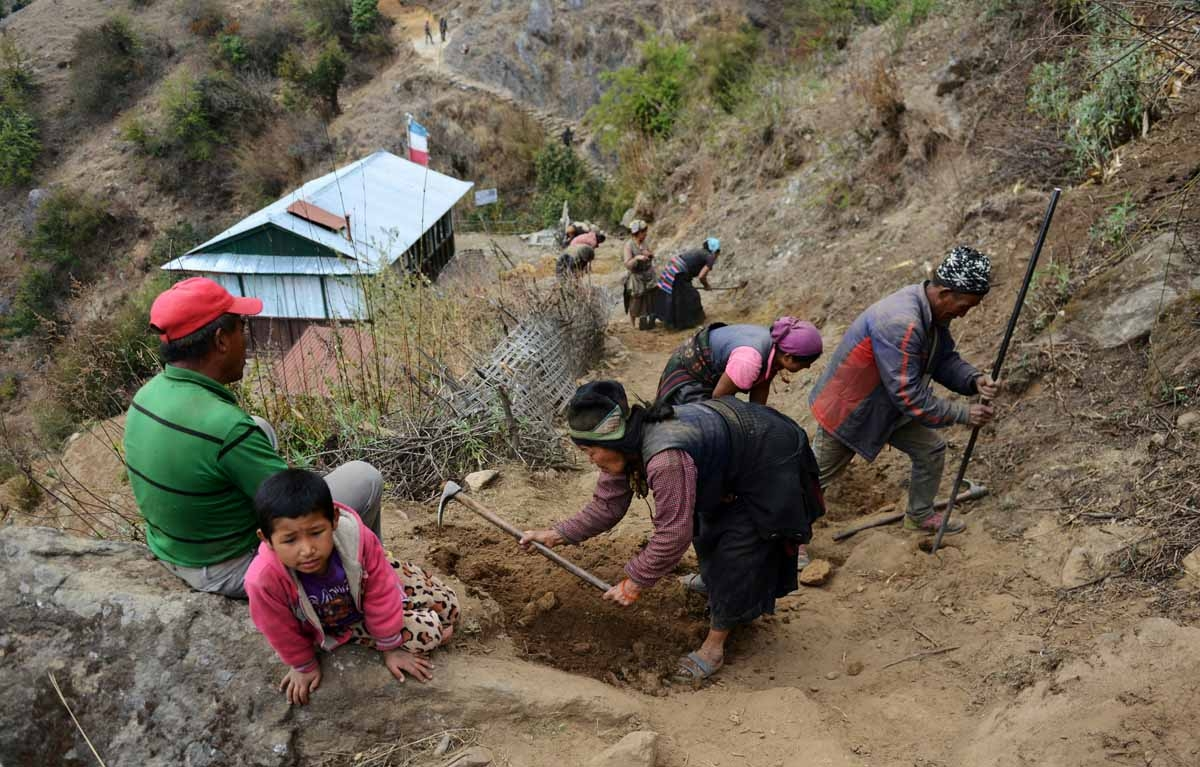 In this photograph taken on April 7, 2016, Nepalese workers restore a trail in Langtang valley in Nepal's Rasuwa district.