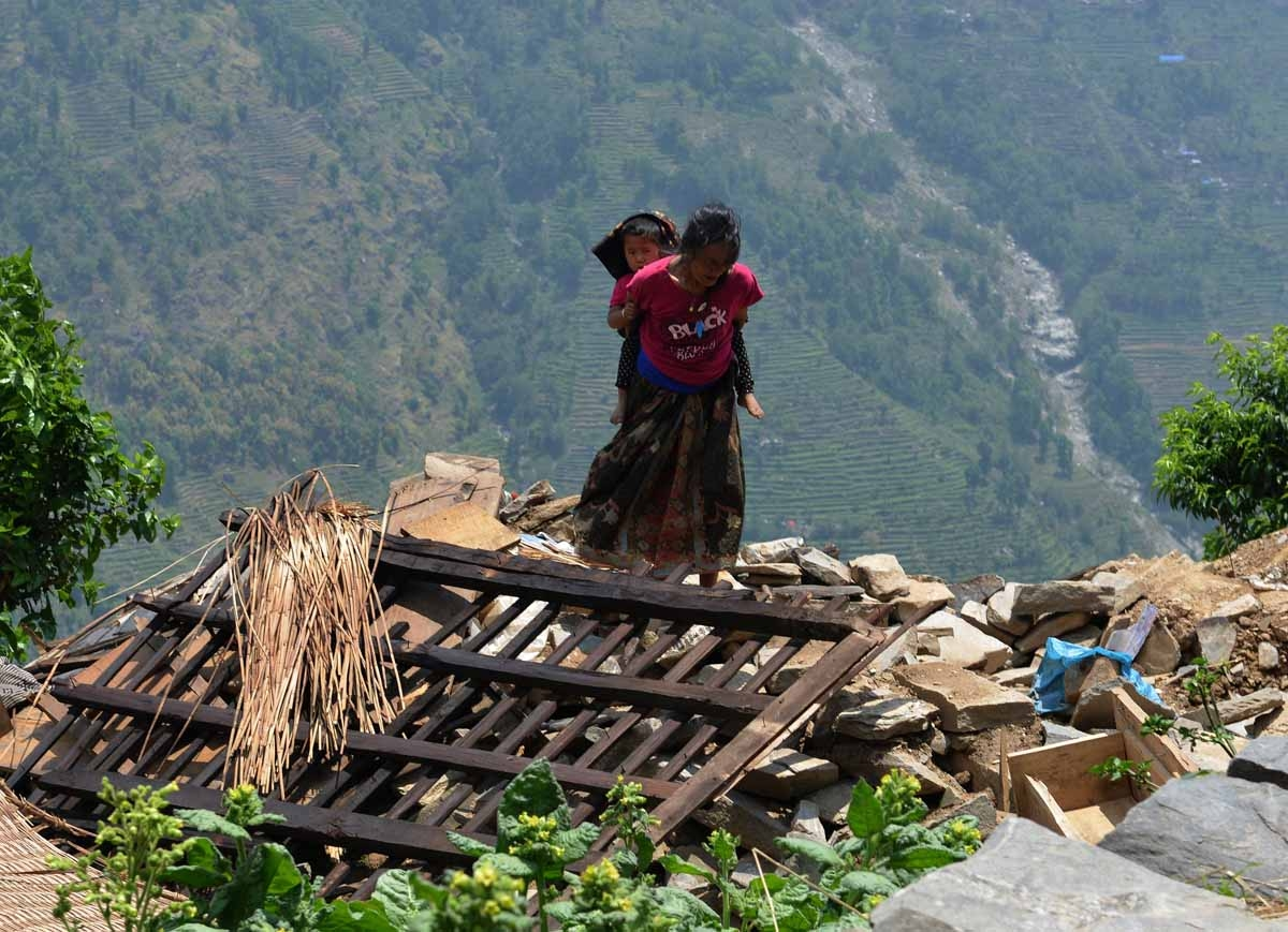 A Nepalese resident carries a child on her back as she walks past damaged homes in the village of Ebi in Dhading district some 60kms north-west of Kathmandu on May 11, 2015.