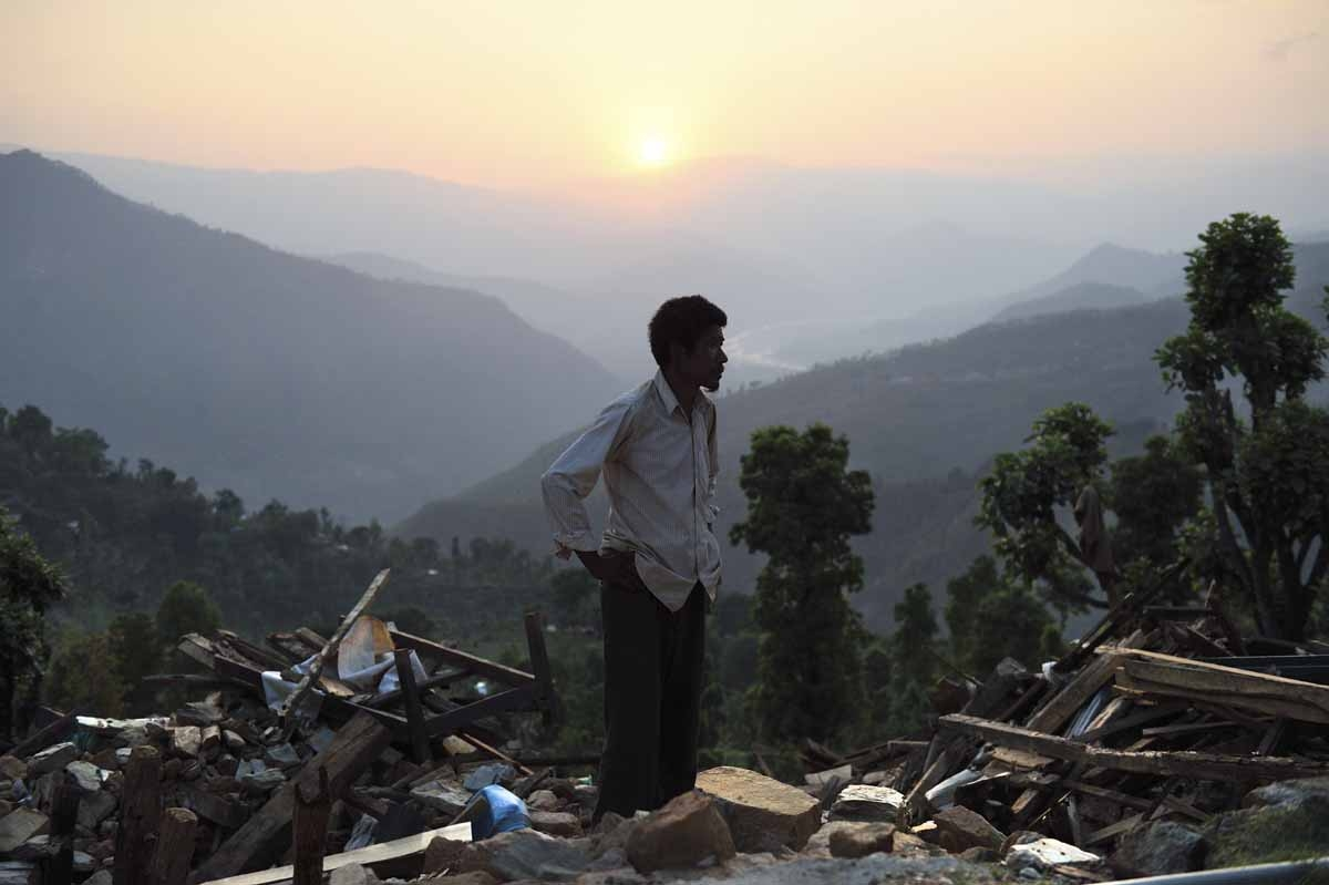 In this photograph taken on May 13, 2015, Ganga Bahadur Tamang stands amid the collapsed remains of what used to be his house in the village of Sangachowk in north-eastern Nepal, two days after after a strong earthquake demolished his home.