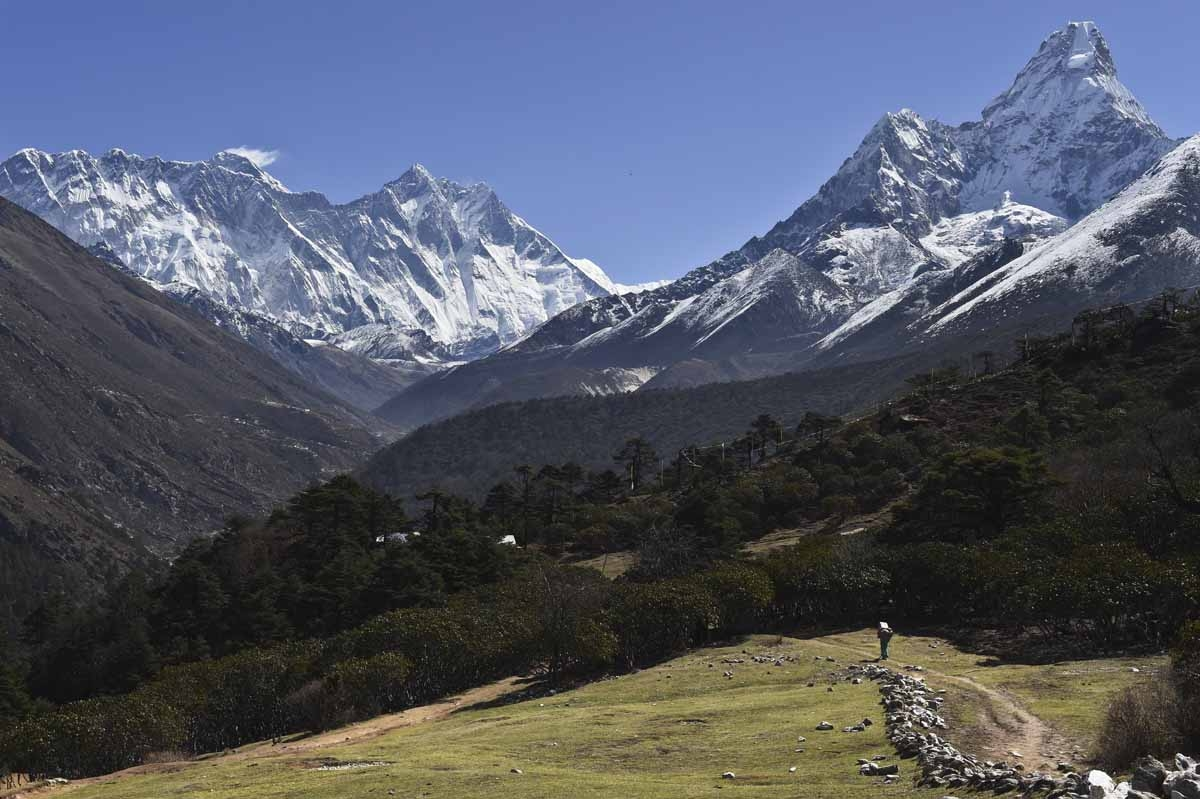 This photograph taken on April 20, 2015 shows a view of a Nepalese porter carrying a load as he walks on a pathway below the Himalayas with Mount Everest (at left with cloud on top), from the village of Tembuche in the Khumbu region of northeastern Nepal.