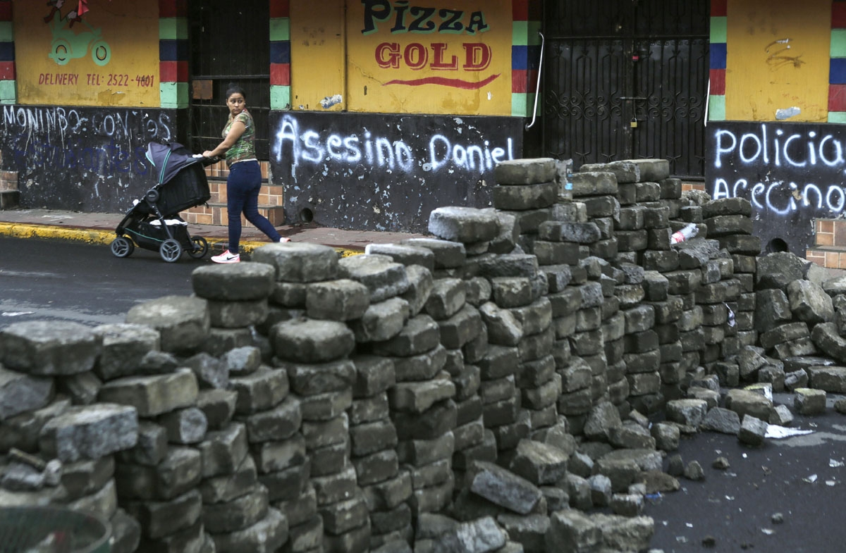 woman looks back after passing by a barricade in the neighbourhood of Monimbo, in Masaya, a city some 35 km from Managua, on May 21, 2018.