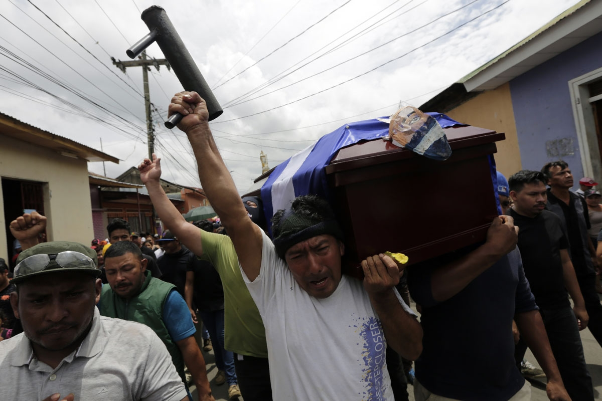 A friend of Jorge Carrion, 33, who was shot dead during protests against the government of President Daniel Ortega, carries a homemade mortar and shouts anti-government slogans during Carrion's funeral in the city of Masaya, 35 km from Managua on June 7,
