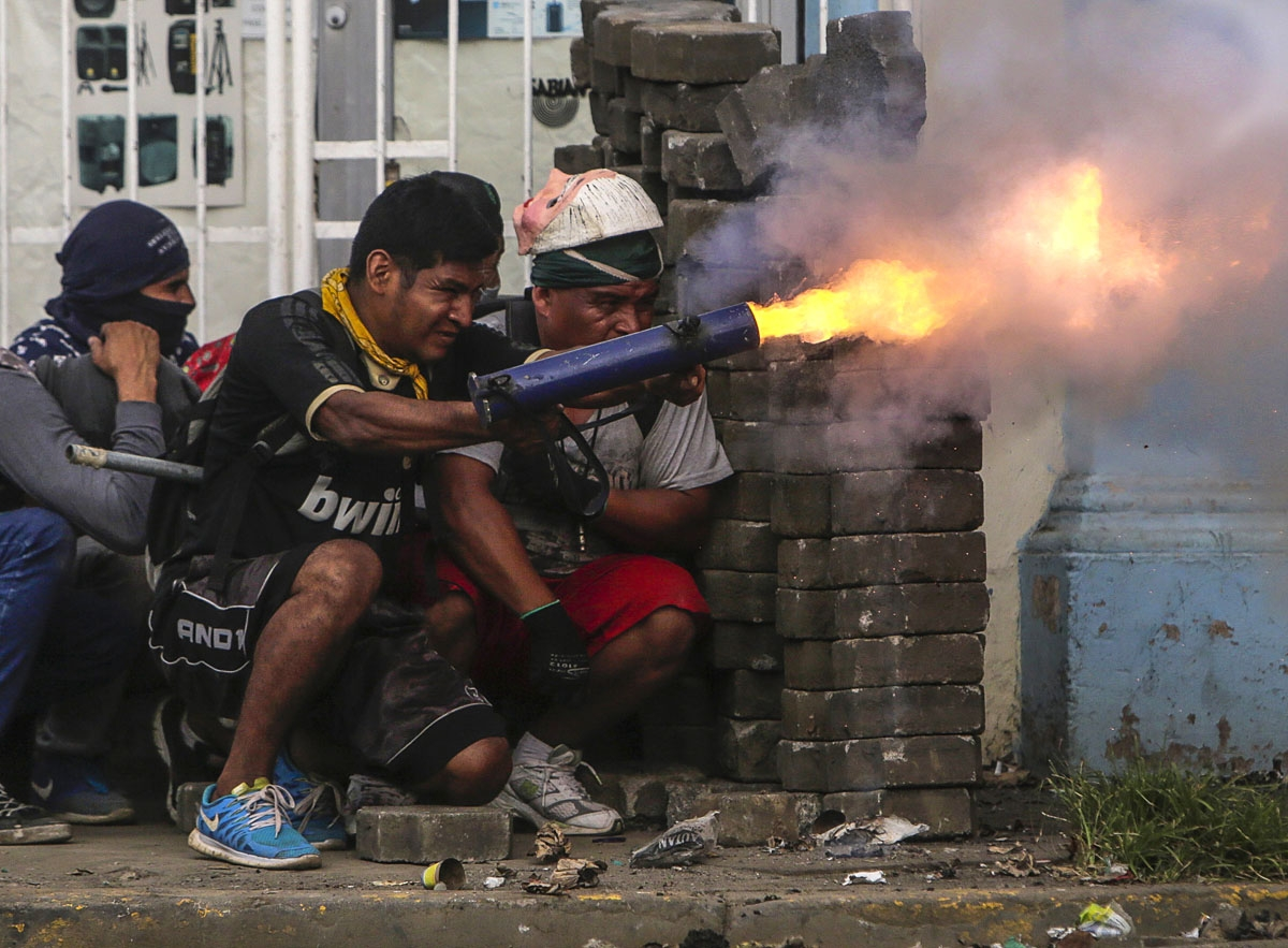 An anti-government demonstrator fires a home-made mortar during clashes with riot police at a barricade in the town of Masaya, 35 km from Managua on June 9, 2018.