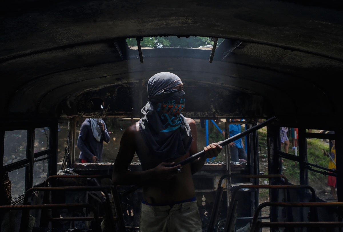 A demonstrator stands inside a bus set alight during a day-long national strike held to mark two months of violent chaos under President Daniel Ortega, in Tipitapa, about 25 km from Managua on June 14, 2018