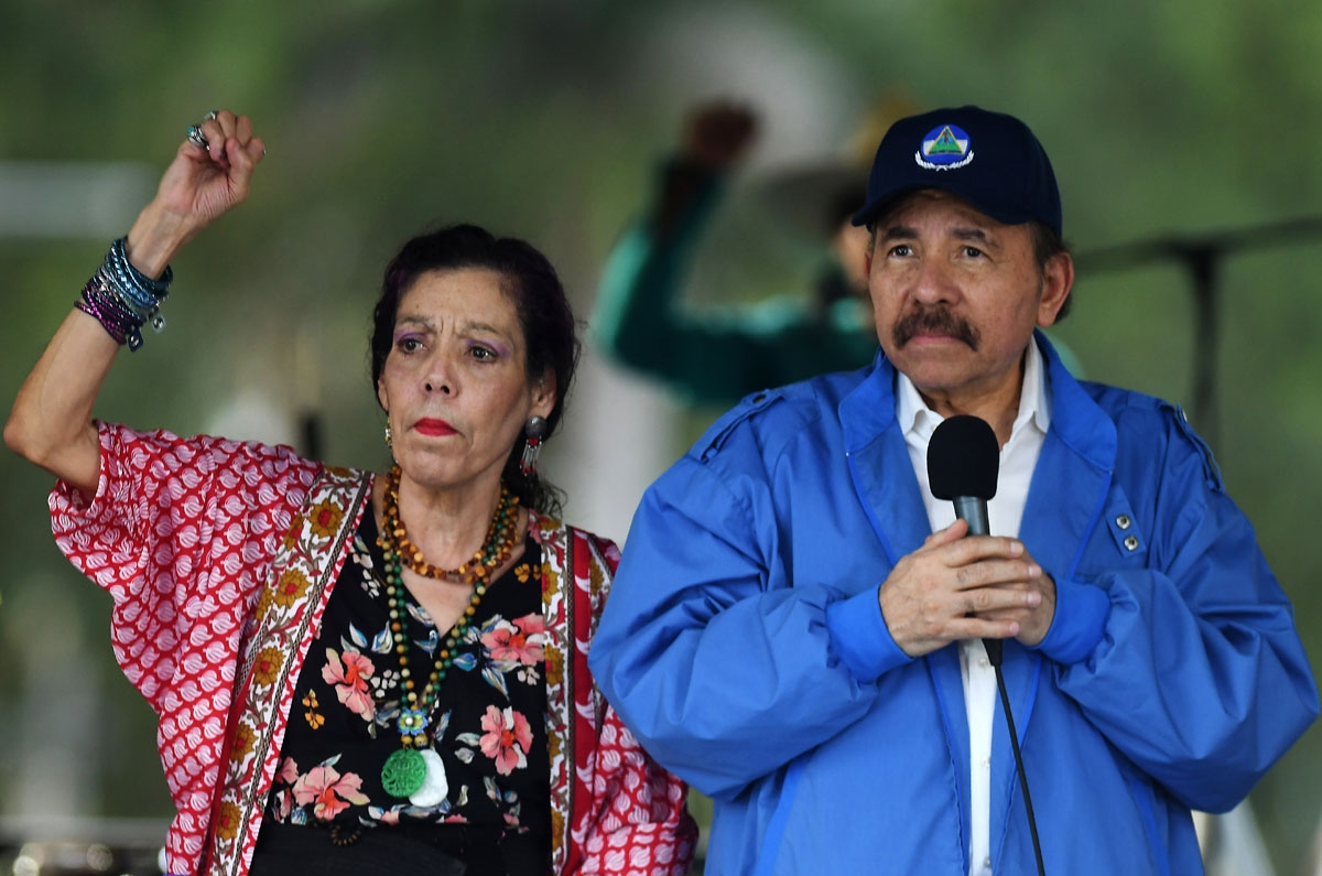Nicaraguan President Daniel Ortega (R) and his wife, Vice President Rosario Murillo, cheer at supporters during the government-called Walk for Security and Peace in Managua on July 7, 2018.