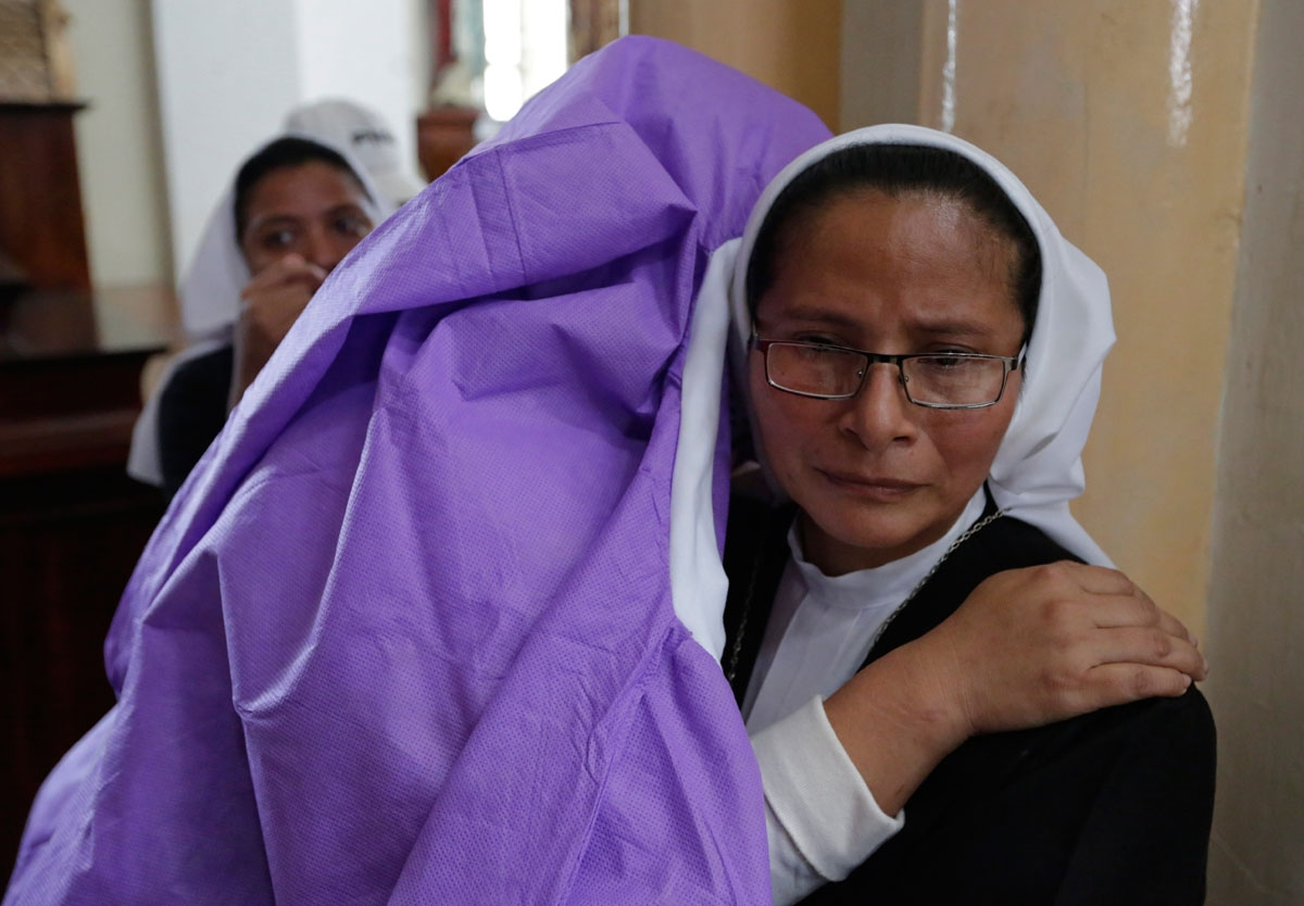 A woman afraid of pro-government Sandinista youths embraces a nun as she takes shelter at the San Sebastian Basilica in Diriamba, Nicaragua, on July 9, 2018. Hundreds of under-pressure Nicaraguan President Daniel Ortega supporters broke into the basilica
