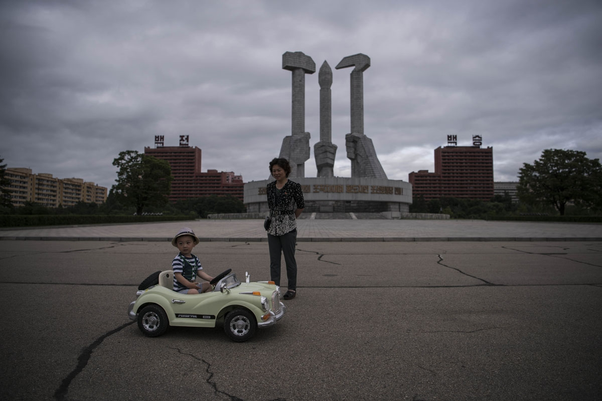 In a photo taken on July 6, 2016 a woman stands before a child driving an electric toy car at the Monument to the Founding of the Workers Party of Korea, in Pyongyang