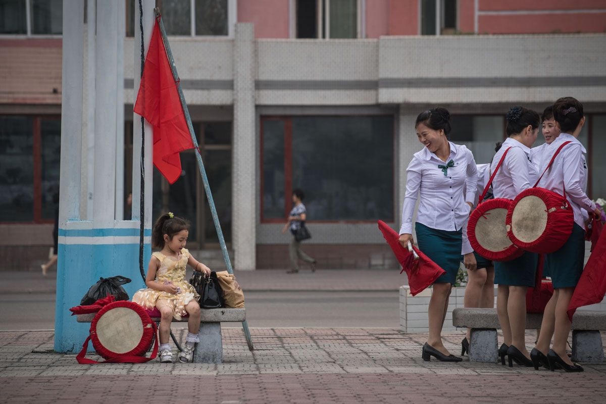 A child waits as members of a local propaganda troupe prepare to perform in a public square as part of a 200 day campaign aimed at kickstarting a new economic plan, in Pyongyang on July 10, 2016