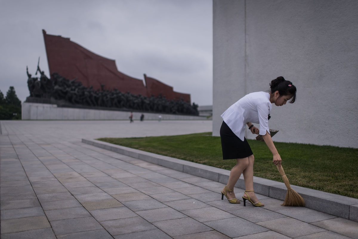 A Pyongyang resident undertakes volunteer work as she sweeps around statues on Mansu hill in Pyongyang on July 13, 2016