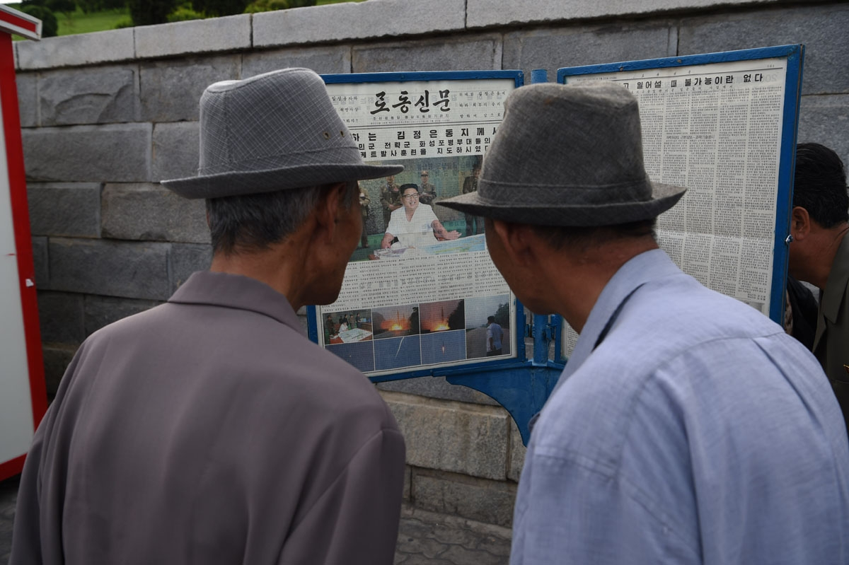 Two men read a copy of the Rodong Sinmun newspaper showing coverage of North Korean leader Kim Jong-Un overseeing a ballistic missile test conducted by the Hwasong artillery units of the KPA Strategic Force, in a public square in Pyongyang on July 20, 201