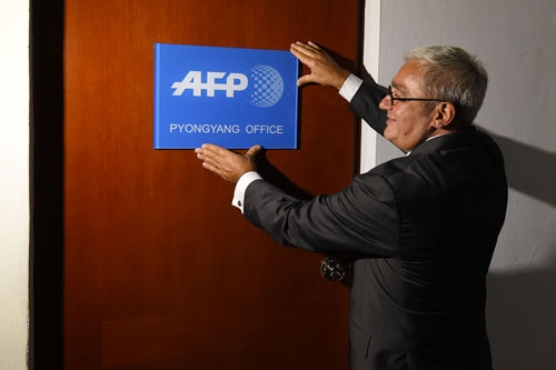In this picture taken on September 6, 2016, Chief Executive and Chairman of Agence France-Presse Emmanuel Hoog hangs a company sign on the door of the news agency's bureau in Pyongyang